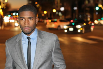 Dapper gentleman outside at night in the city looking away while strolling around Downtown