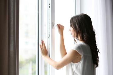 Beautiful woman opening window in the morning Wall mural