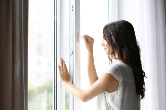 Beautiful woman opening window in the morning