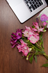 Laptop on wood floor with flowers. alstroemeria