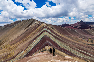 Tourists couple stand and look afar at Rainbow Mountains, Cusco, Peru.