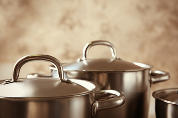 Kitchenware concept. Stainless saucepans on grey textured background