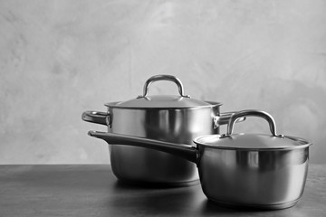 Kitchenware concept. Stainless saucepans on table and grey textured background