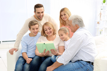 Happy family reading book while sitting on sofa in living room