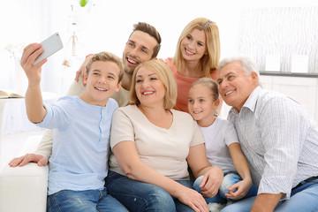 Happy family taking selfie in living room