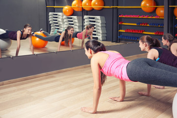 Young sporty women training with fitness balls in gym