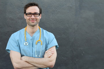 Handsome doctor smiling and laughing with copy space