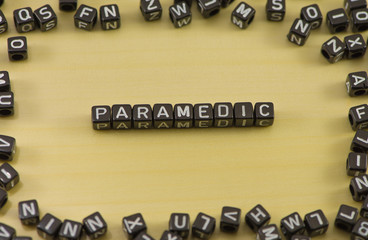 Word paramedic on wood background