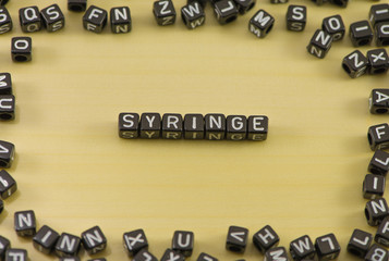 Word syringe on wood background