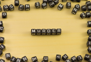 The word murder on wood background