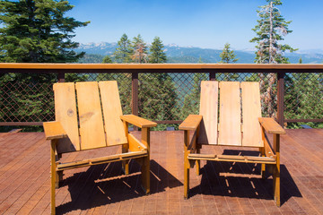 Two wood chairs on outdoor sunny deck with mountains in the background