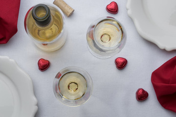 2 glasses of white wine with bottle, cork, and candy on a red and white table setting