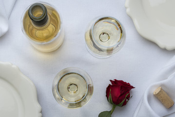 2 glasses of white wine with a bottle, cork and rose on a white linen table setting