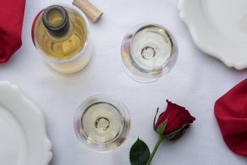 2 glasses of white wine with a bottle, cork, and rose