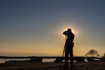 Silhouette of photographer taking photos in the mountains. Filter effect style