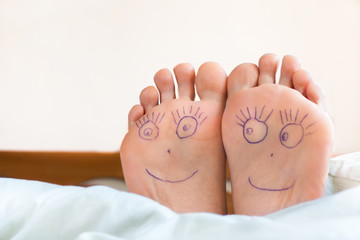 Pair of female feet with smiling faces on it.