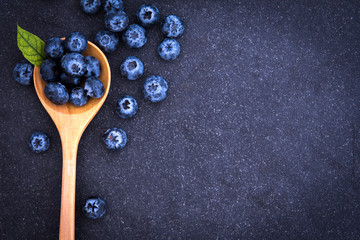 fresh picked blueberries in wooden spoon on black stone