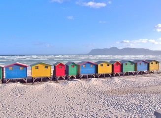 Colorful beach huts at Muizenberg near Cape Town, South Africa. Sea ,Sand and blue sky as background. Muizenberg is a beach-side suburb of Cape Town, South Africa.