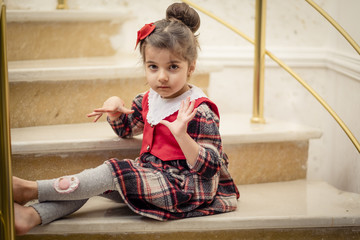 Small Iraqi girl sitting on marble stair inside house