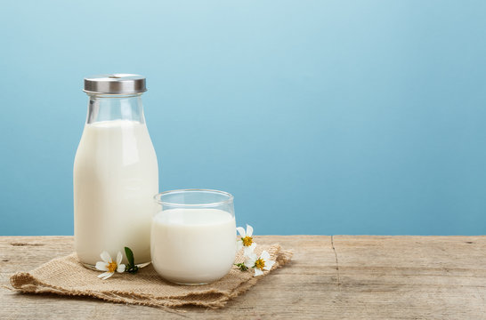 A bottle of rustic milk and glass of milk on a wooden table on a