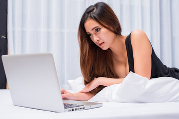 woman and laptop on bed, woman and notebook on bed, woman and computer