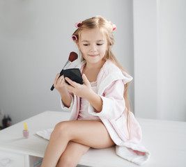 Little girl with long blond hair and brown eyes, wind the hair on the big pink curlers, holding in his hand a black powder compact and a large brush for makeup, sitting on a white table