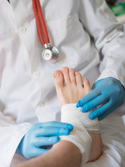 close up of doctor bandaging one injured foot