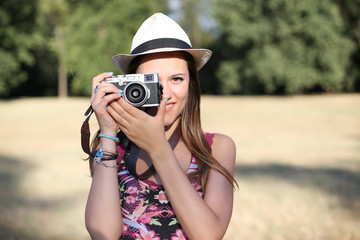 beautiful brown hair girl with white panama hat while shooting a picture with her camera at park in a sunny day. summer portrait
