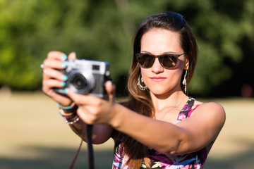 beautiful brown hair girl while shooting a picture with her camera at park in a sunny day. summer portrait