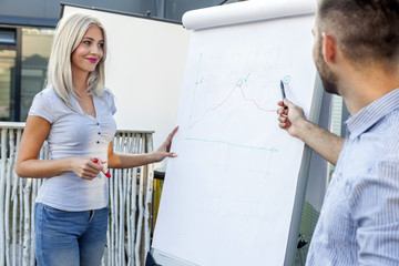 Business people analyzing data together on flip chart