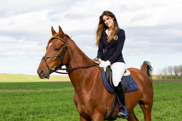 Beautiful young girl in uniform competition rides with safety her brown horse and smiling: outdoors portrait on sunny day