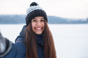 Young beautiful woman taking selfie photo in winter snow park near frozen lake