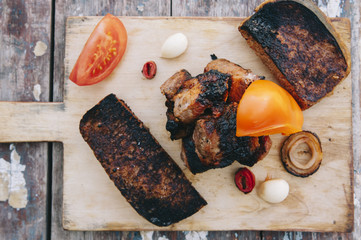 Delicious meat kebab on the wooden board with a barbecue toasted bread, pepper and onions on the wooden table background