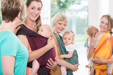 Gruppe von Frauen lernt Umgang mit Babytragetüchern für Mutter-Kind-Bindung