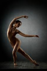 girl dancing barefoot. ballet. grey background