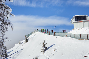 People skiing on the ski slope covered with snow in the winter season in the mountain resort of Poiana Brasov, Romania