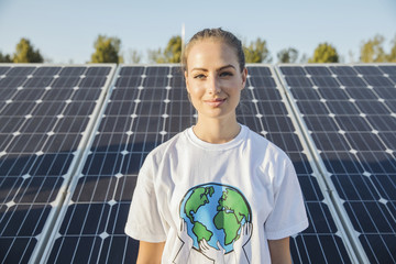 Portrait of teenage environmentalist in front of solar panels