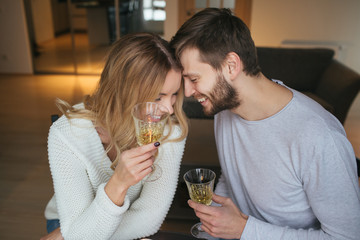 Smiling pair talking and holding wine glasses