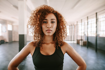Beautiful afro american female with curly hair in gym