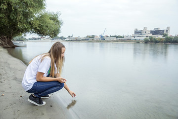 Teenage girl taking a water sample out of river