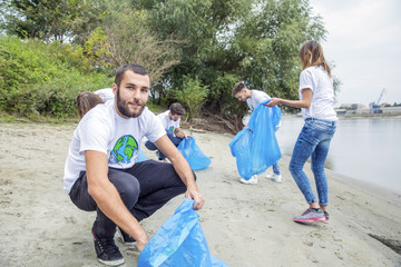 Teenage volunteers doing garbage cleanup on riverbank