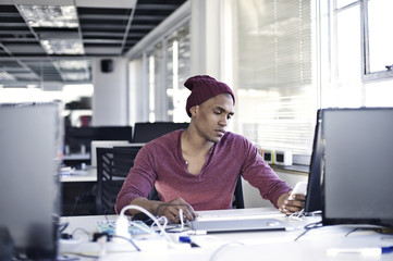 Black male creative professional with mobile phone in an informal office