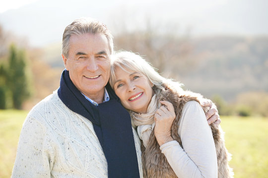 Portrait of cheerful senior couple enjoying day in countryside