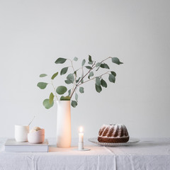 Cake with candle and vase on table