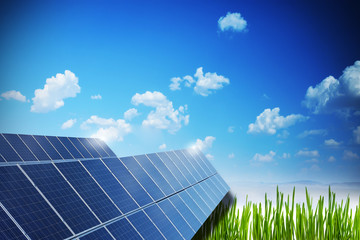 Solar panel field with blue ski and green grass