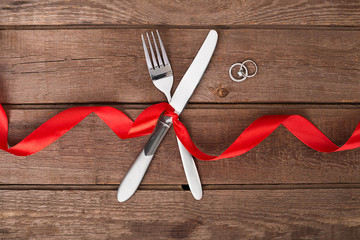 Valentine's Day dinner table setting with red ribbon, knife and fork  ring over oak background.