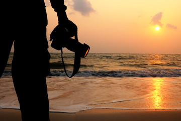 photographer with a camera and a red sky sunrise on the beach.