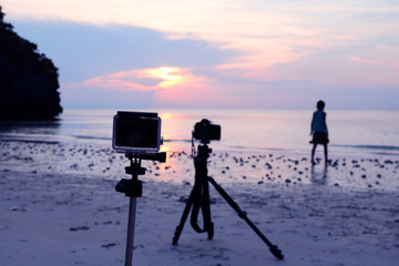 camera and tripod at the beach with a background image of girl with the sunset.