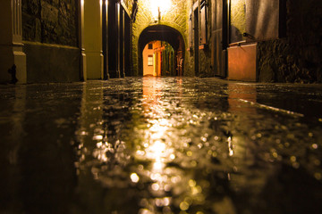 Wall Murals Narrow alley Focus on wet ground along dark medieval alley on a rainy night, Butter Slip, Kilkenny Ireland.
