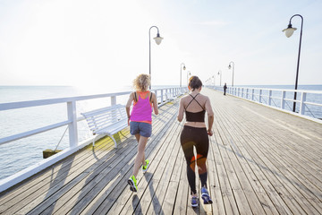 Two women jogging along a jetty